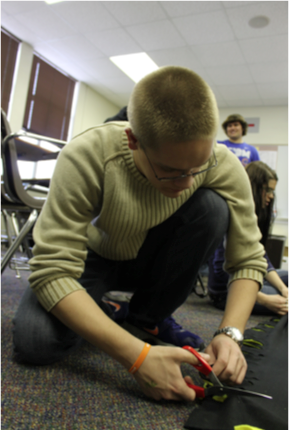 Junior Nathan Eggleston cuts ties in the fleece blanket his advisory was making.