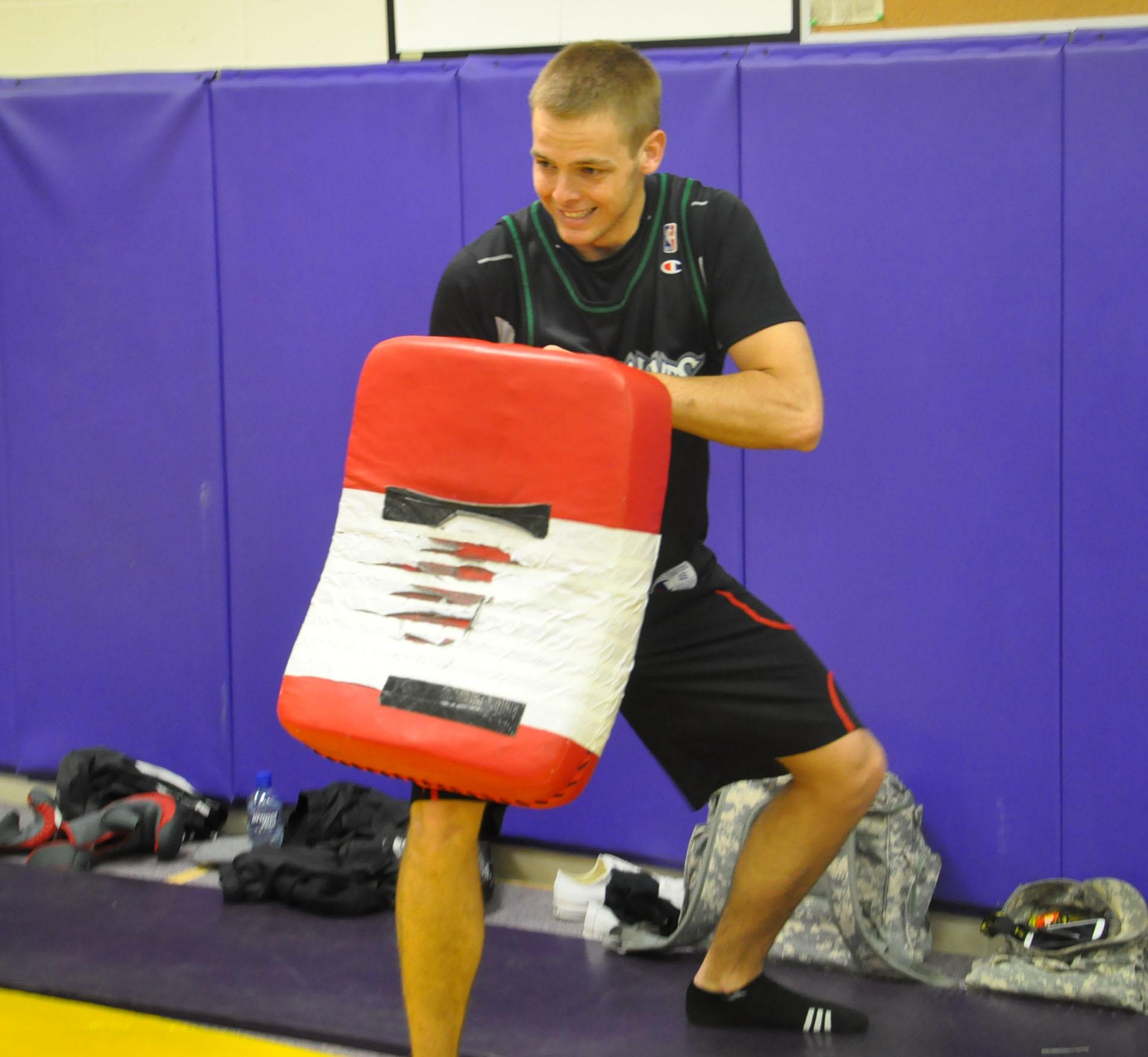 Senior Joe Hawks prepares to embrace a kick from a student during the self-defense class on March 14. The class also included activities such as punching, swing kicks, and knee punching.