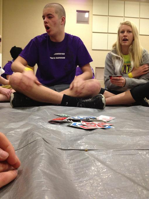Waiting for the boys state swim meet to start, junior Carter Mehls and senior Victoria Trost play UNO.  A large group of students, mainly boys and girls swimmers, camped outside of the Marshalltown YMCA the night before the meet so they could get good seats in the morning.