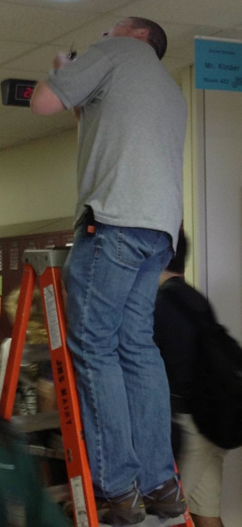 Custodian+Jay+Nickolash+inspects+the+smoke+detector+after+students+were+given+the+clear+to+come+back+into+the+school.