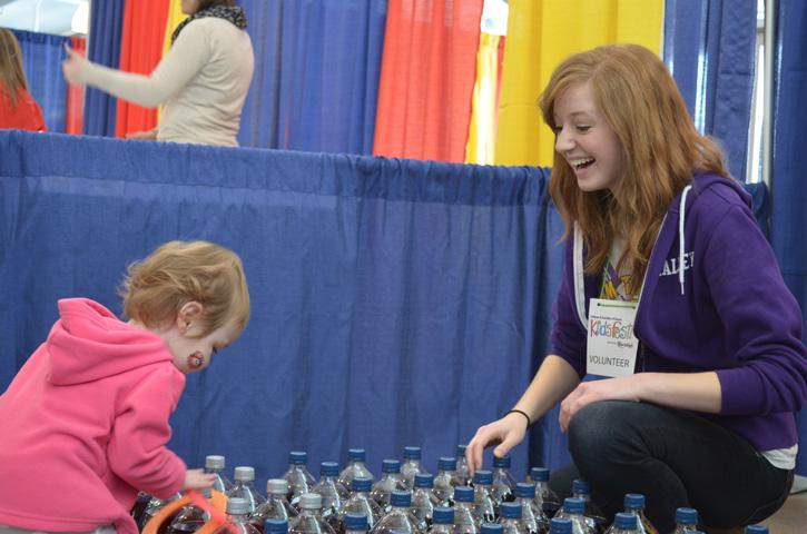 Enjoying a toddler at the Pepsi/Quaker ring toss station, Senior Laura Smalley encourages Kid's Fest participants as they attempt to throw a toy ring around a pop bottle. The Kid's Fest took place in the Varied Industries Building at the Iowa State Fairgrounds March 1-3.