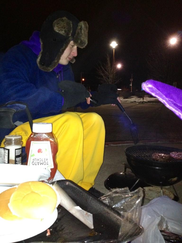 Freshman Seth Schieffer trys to stay warm by cooking hamburgers and hotdogs outside of the Marshalltown YMCA at the boys state swimming campout.