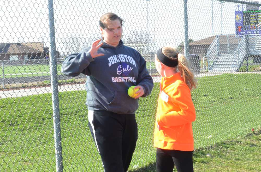 Senior+Kim+Hughes+instructs+a+Little+Dragon+participant+on+throwing+a+shot+put.+The+coaches+started+off+teaching+with+a+softball+to+help+the+participants+get+a+feel+for+the+technique.+