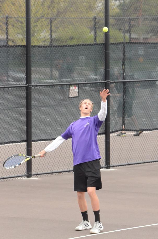 Senior Justin Atterberg is in the midst of a serve at district tennis held at the Johnston High School tennis courts.