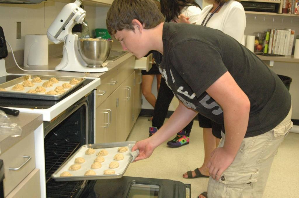 Junior Mitch Jaworski puts a batch of cookies into the oven during culinary class. The class baked a variety of cookies ranging from peanut butter to chocolate chip.
