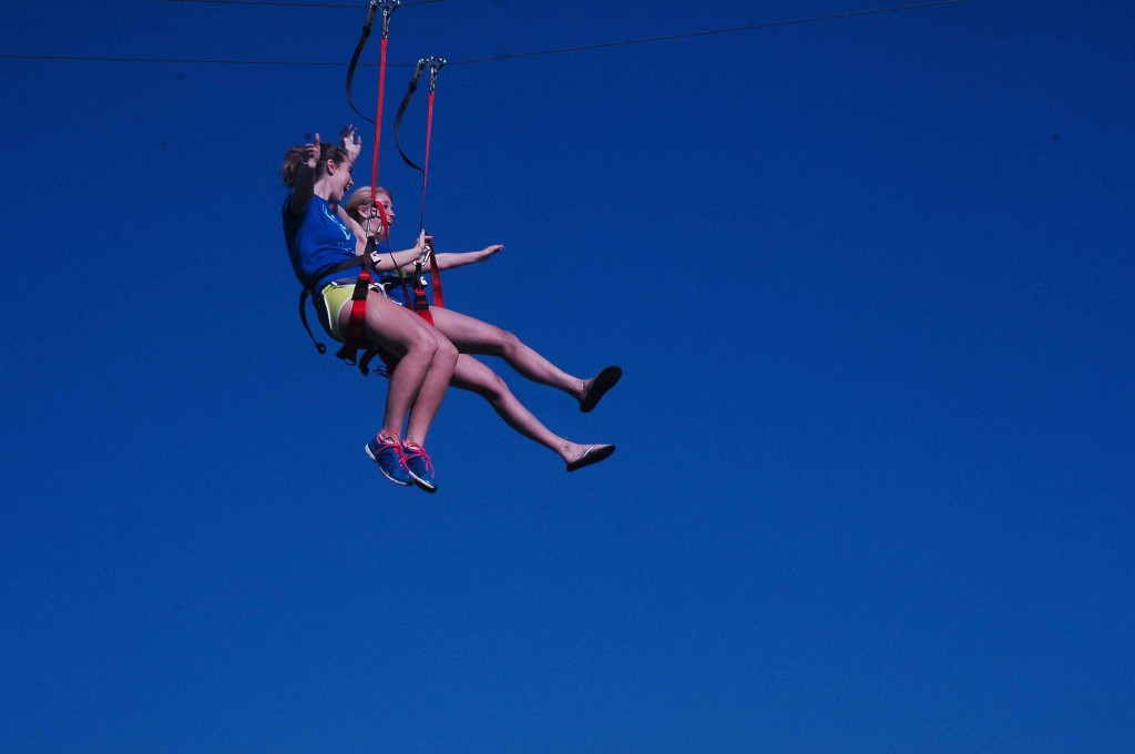 Seniors+Laura+Schwartz+and+Bailey+Pierotti+zipline+during+PE+third+period+on+Sept.+26.+The+Iowa+National+Guard+brought+a+zipline+and+rock+climbing+wall+for+all+the+PE+classes.