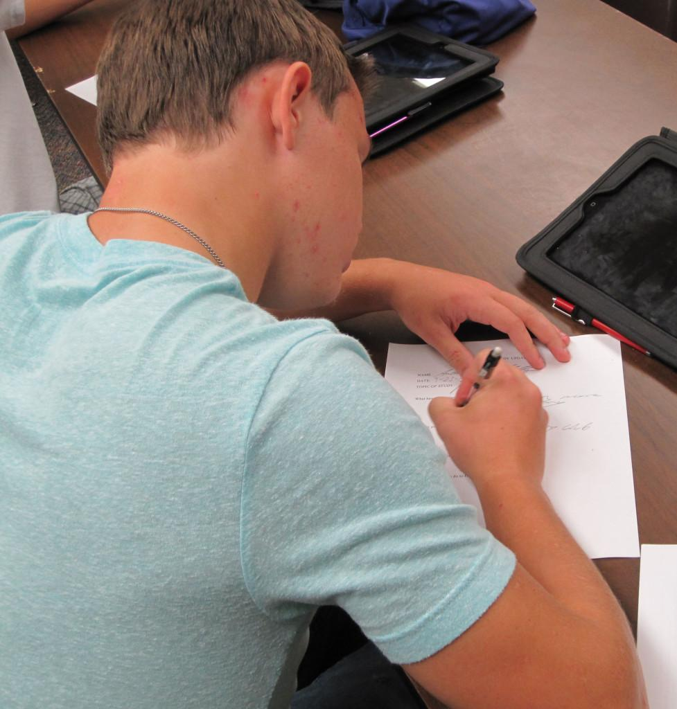 Senior Andrew Mills fills out paperwork needed for poetry club to be approved. He has been working hard to get poetry club to be approved, and hopes to have the first meeting in October.