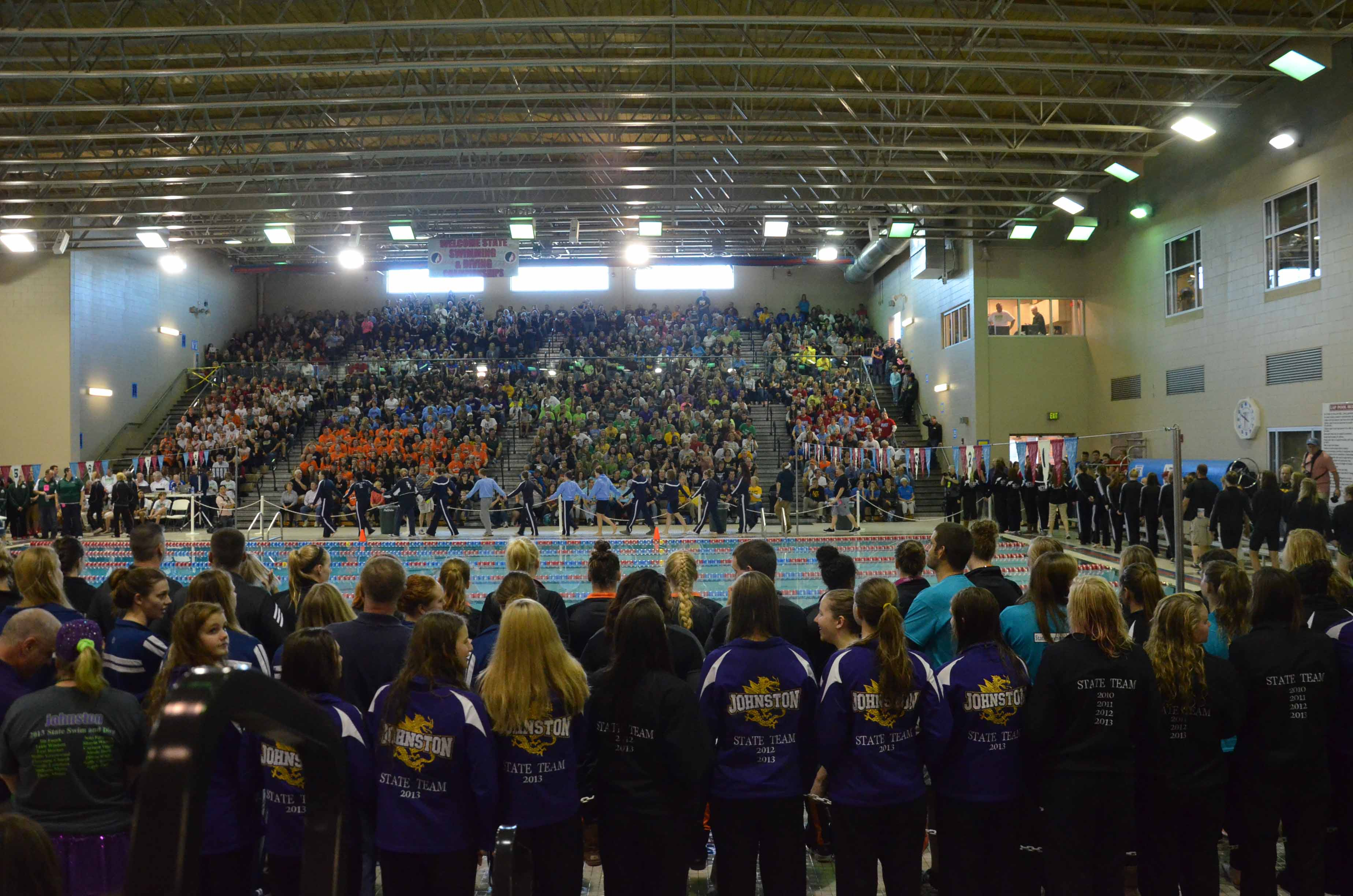 The girls' swim team lines up as they await to be announced during the parade of teams before the state swim meet. The team placed 10th overall and had 15 swimmers qualified to swim, the biggest state team head coach Shari Walling has ever had.