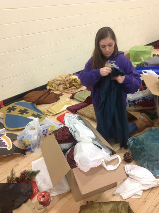 Junior Alize Olson sorts through decorative fabrics for the Madrigal setup during her 7th hour service credit. Madrigal performances were on Friday December 6 and Saturday December 7.