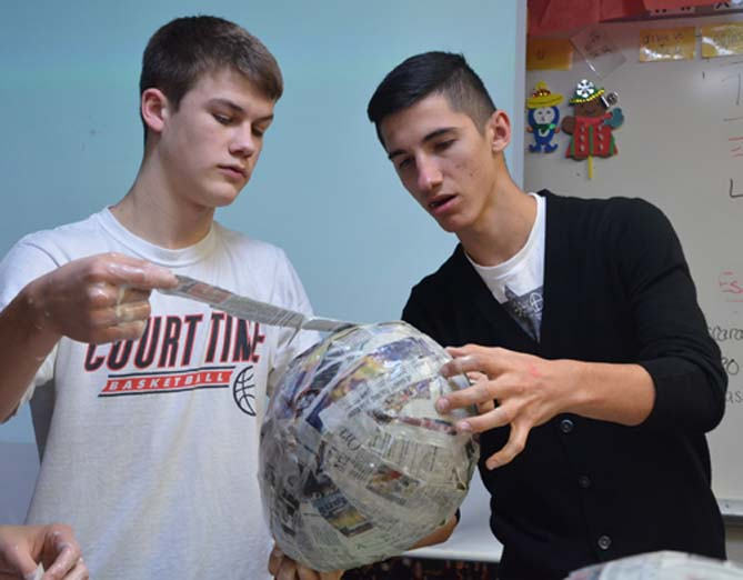 Sophomores+Drake+Moser+and+Elvir+Ibisevic+finish+covering+their+balloon+with+the+treated+newspaper+with+the+last+strip.+Moser+and+Ibisevic+hope+to+make+their+pi%C3%B1ata+into+a+beehive.+
