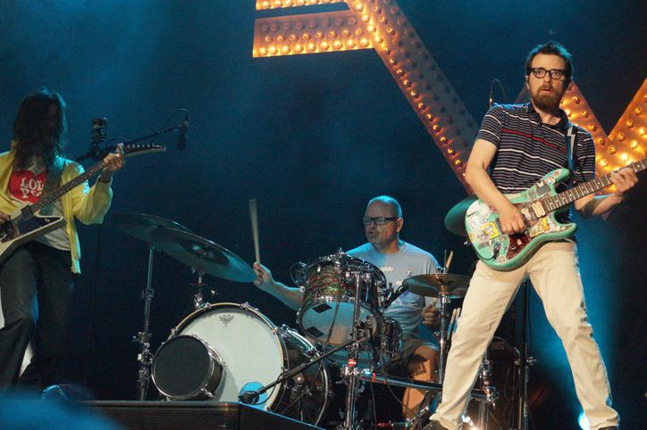 Gathering upstage during Weezer's performance, lead singer and guitarist Rivers Cuomo [right] along with bassist Brian Bell [left] stand on either side of drummer Patrick Wilson [center]. The three have played together since 1993, when Bell joined the band.