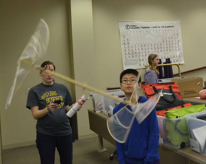 Eighth+grader+Bradley+Qin+and+middle+school+science+teacher+Liz+Herzmann+look+on+at+an+elastic+powered+helicopter%2C+testing+to+see+how+long+it+stays+in+the+air.+Qin+did+not+place+with+his+helicopter.