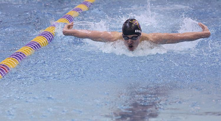 While performing the 100 yard butterfly, senior Ben Kramer surfaces for a breath. The boys swim team placed second in the District swim meet Feb. 6.