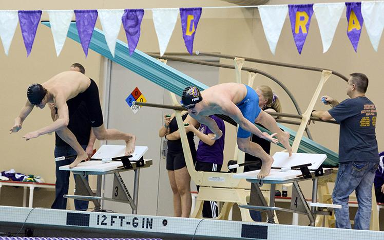 Junior Grant Fuhr dives into the pool during the 100 yard freestyle. The boys swim team placed second in the District swim meet Feb. 6.
