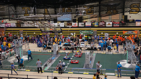 Six teams assemble on the field to compete in a match at the CowTown ThrowDown Robotics event. These teams come from four states and may compete with each other at other events during the year.
