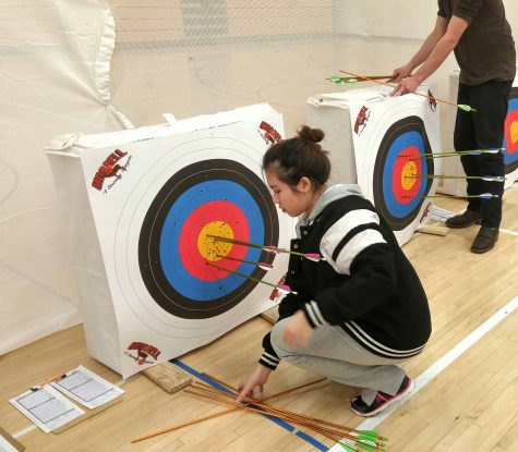 Archer Vivan Nyugan '19 picking up the arrows she pulled from her target. She had two arrows in the yellow even with this being her first tournament.