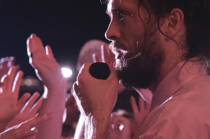 After allowing a fan to sing one verse of a song, vocalist Alex Ebert stands just outside the barricade to sing near the crowd. Edward Sharpe and the Magnetic Zeros performed Friday, July 31 at 9:30 pm.