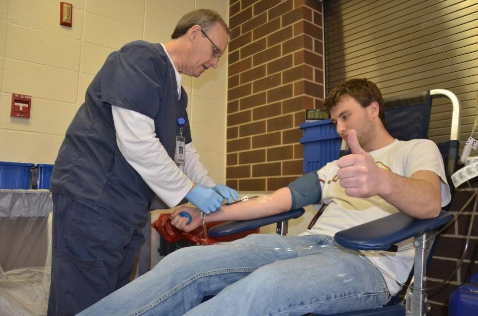 Junior Jon Dolan nervously gives a thumbs up while watching his blood being drawn from his arm.