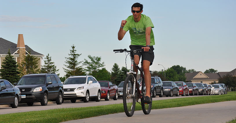 Jake Perrington rides his bike in front of the runners to show the route during the 5k.