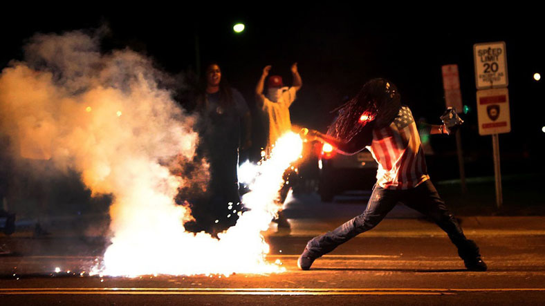 This photo has become iconic as the official photograph of the Ferguson protests, showing a man throwing a tear gas container away from the protesters near him.