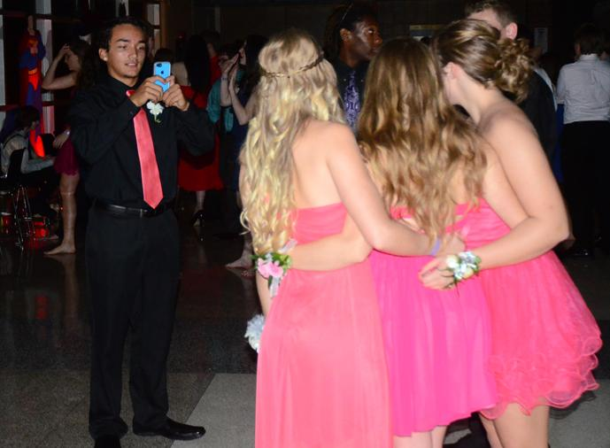 Sophomore Anthony Calaway takes a picture of three girls in similar dresses. The dance was held Sept. 27 at Summit.