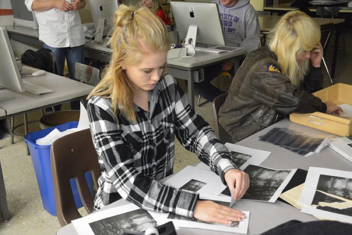 Tearing a print of her photograph, senior Lexi Thompson prepares to create a French Collage.