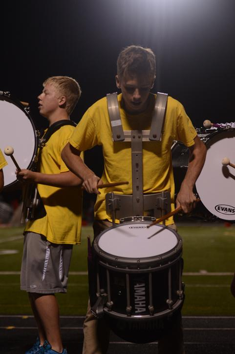 Senior Ross Kromminga hits the snare drum with the drumline next to the field. The band scored