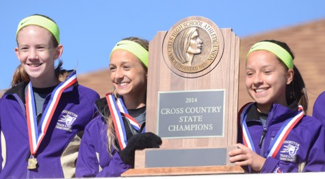 Seniors Jordyn Kleve and Sandra Kromminga, along with junior Sara Ness hold up their state champion trophy after winning the state meet Nov. 1. This is the first state title in the girls' cross country history. Kleve ran a time of 14:14, which is the fastest in Johnston history.