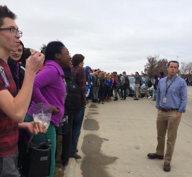 Science teacher Chris Siewert directs students off of the street as they evacuate the building.