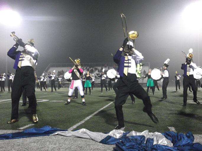 Senior Brian Brass and junior Adam Dostalik play their instruments along with the rest of the marching band at their final half-time show of the season. Marching band had a successful season, even placing first at the Iowa City and Waukee Marching Invitationals.