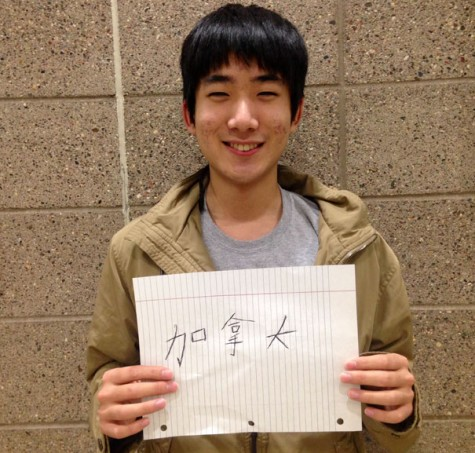 Junior Michael Tan holds a sign that says 'Canadian' in traditional Chinese characters to represent his identity in both cultures.