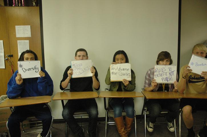 The design team holds up signs stating what they want to talk about during in-service days.