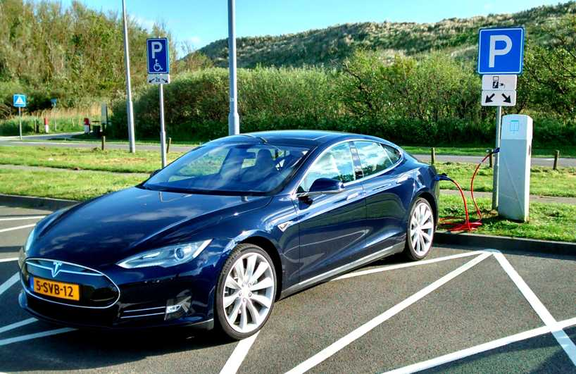 Model S of the Tesla motors line of four door vehicles. It is plugged into a charging station where it is gaining miles.