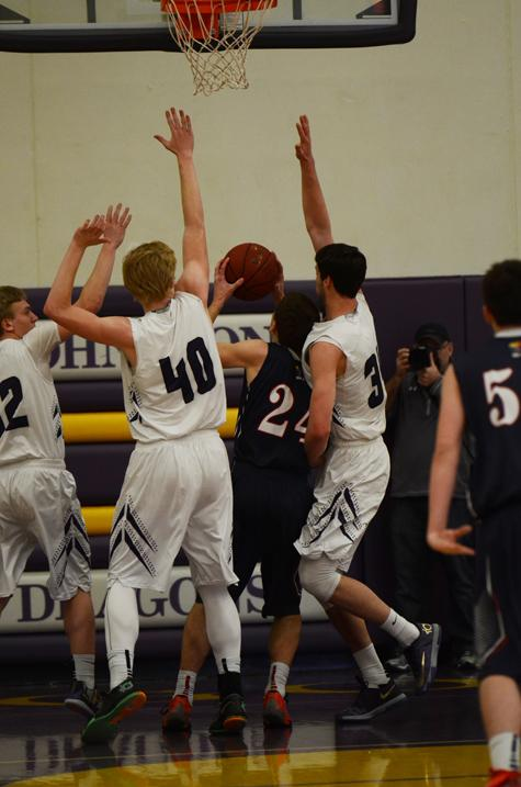 Junior Jared Bacon, and seniors Regen Siems and Derek Jones block an Urbandale player from making a shot. Derek ended up getting his 2nd foul from blocking the player.
