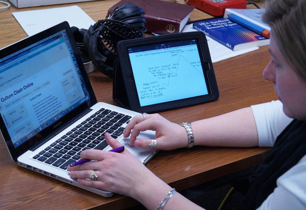 English teacher Sarah Moore checks student's assignments from the online Culture Clash course. Moore is able to communicate with students through showbie, moodle and email for feedback and discussion.
