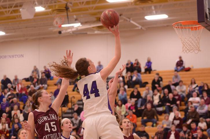 Guarded by a Dowling Catholic Maroon player, sophomore Taryn Knuth attempts a layup Feb. 6. The Dragons have played Dowling Catholic three prior times in the season.