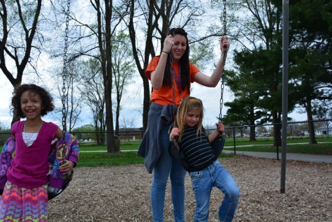 Senior Sam Wilkinson pushes two girls on the swings at the Lawson Elementary School playground during her shift at Kids/Teen Connection (KTC). Wilkinson has been working at KTC since September 2014 and thoroughly enjoys building relationships with the kids she works with.