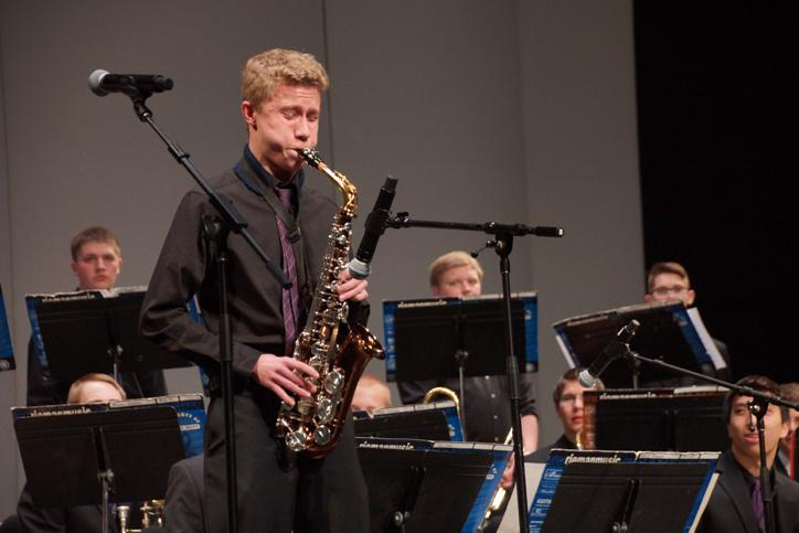 Sophomore Kyle Burgess plays his alto saxophone solo during the song