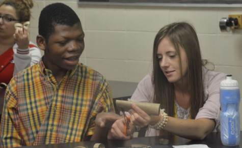 Senior Scarlett Eagle works with sophomore Meschac Ntambwe to cut up their paper roll. Eagle uses the hand over hand method so Ntambwe can interact. The project was made but cutting up toilette paper rolls and gluing them together tho make flowers. Peer art is everyday during seventh and students rotate between art and P.E.