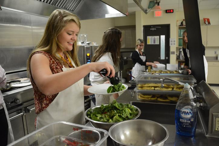 Tossing the salad, senior Aly Bowen prepares a side dish to serve to staff members April 9.