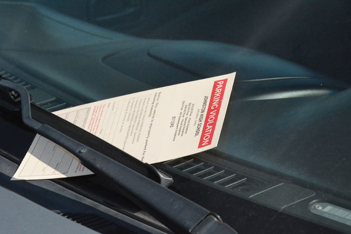 The ticket is placed between the windshield and windshield wipers to signal the student they received a parking ticket. The fee starts at $10 then progresses up to $30.