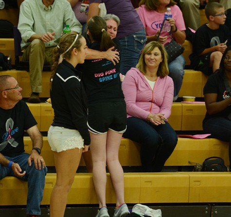 Junior Anna Miller hugs and hands a carnation to one of the standing cancer survivors in the crowd. The girls' varsity volleyball game took down the Urbandale Jayhawks during the Digpink/ Spikeblue game Sept. 29.