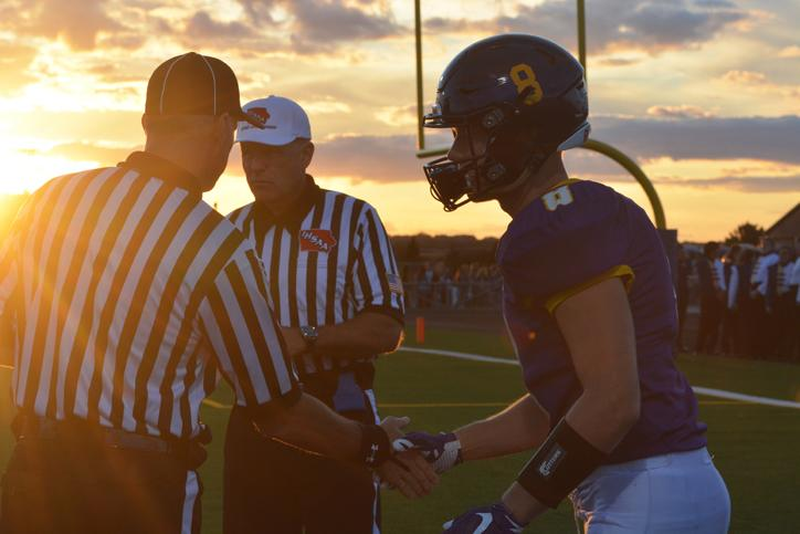 Right+before+the+game+junior+Noah+Edmondson+shakes+hand+with+the+referee+right+as+the+sun+sets+down.+The+varsity+football+team+played+against+the+Urbandale+Jayhawks+Sept.+11+at+home.+