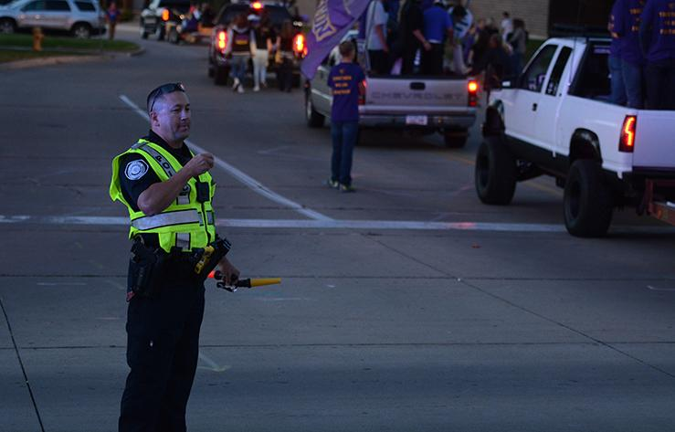 Student resource officer James Slack helps guide the different parade floats thought the streets. The homecoming parade started across from Panera and ended at the high school Oct. 1 starting at 6 p.m.