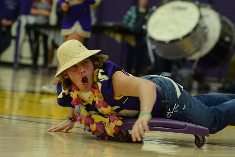 Senior Nolan Monthei yells at the crowd while rolling across the floor on a scooter to compete in the obstacle course. The pep assembly was right after third period Oct. 2 with homecoming festivities such as a teacher lip sync battle and obstacle course.