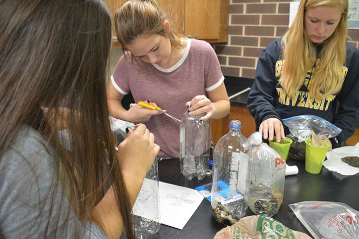 Sophomores+Jordan+Durst%2C+Sydney+Hughes+and+Melinda+Nguyen+cut+open+their+bottles+to+place+the+dirt+and+rocks+inside.+Their+next+observation+is+Oct.+28%2C+and+the+observations+will+continue+weekly+until+Nov.+23.