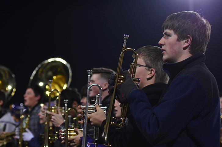 Preparing to play the national anthem before the game senior Jacob Kraber stands in the brass section with his trumpet. The varsity football team played the third playoff against the Valley tigers Nov. 6.