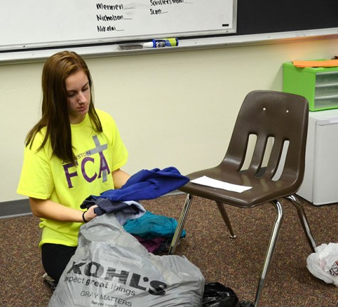 Junior Anne Krone folds clothes that were donated to the drive. The students that helped fold the clothes tallied up the amount of clothes each room donated to select the winner.
