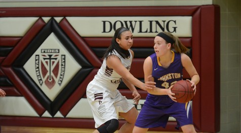 Senior Rachel Hinders dodges a Dowling player during their game before the varsity boys' Dec. 11. The girls' kept up their undefeated streak 6-0, after winning the game 51-42.