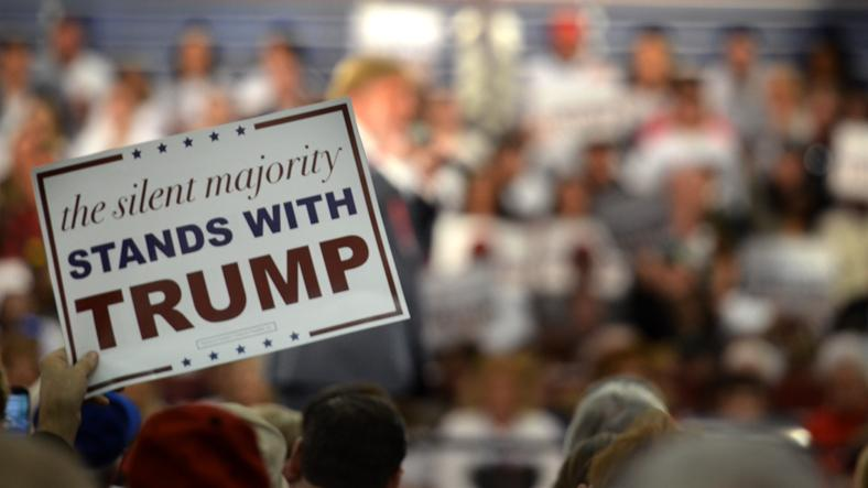 An audience member holds up their sign as Trump speaks. The signs were distributed to all guests before the rally, which took place Dec. 11 at the Iowa State Fairgrounds.